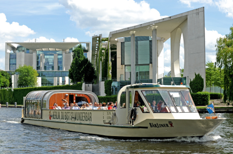 A boat on the river Spree with the Chancellory in the background. Photo: DPA