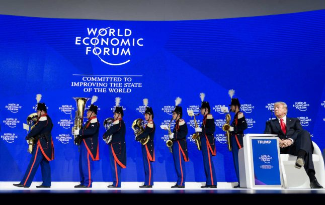Boos and brass band greet Trump in Davos