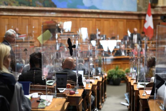 Switzerland installed plexiglas boxes in parliament to protect politicians when sessions resumed in autumn of 2020. Photo: Fabrice COFFRINI / AFP