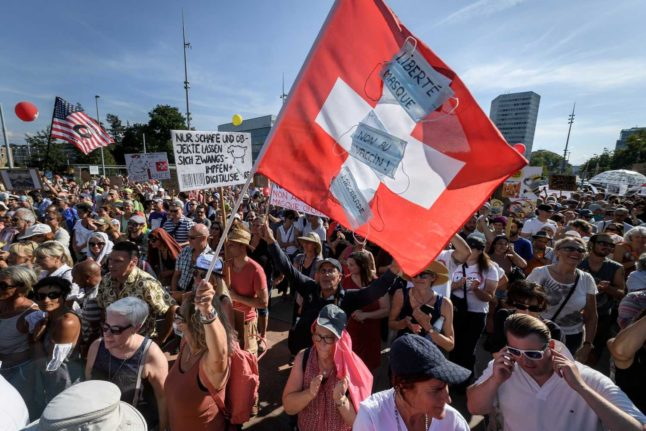 A demonstrator wave a Swiss national flag during a protest against coronavirus measures in Geneva. Photo: Fabrice COFFRINI / AFP