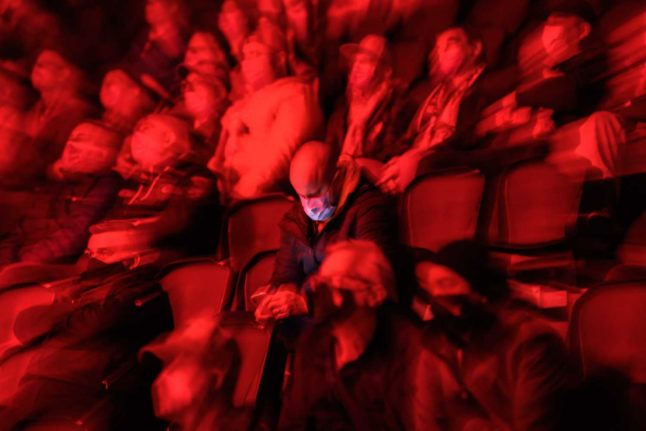 A spectator wearing a protective face mask uses his smartphone during the Swiss National League ice hockey match between Lausanne HC and SCL Tigers in Lausanne on October 1, 2020. Switzerland allowed 1,000 people to attend events from October onwards, before quickly backtracking as a second wave of the virus swept across Europe and the world. Photo: Fabrice COFFRINI / AFP