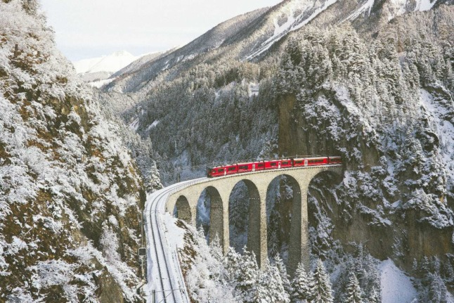 A red train carves its way though the Swiss mountains on a snowy day.